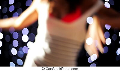 a sexy woman dances out of focus with disco lights in...