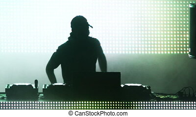 shot of a dj looking playing at a festival in front of a...