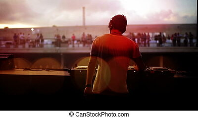view from behind a dj looking out to the crowd at a festival