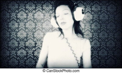 a super sexy woman dances wearing headphones with a classic wallpaper background
