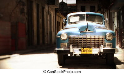 timelaspe of a classic car in the street with people walking past in havana, cuba