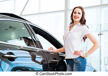 young woman standing near a car - attractive young woman...