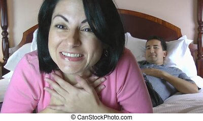 Couple at home using online technology to video chat with...