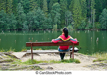 Thinking - Woman sitting on a bench near the lake