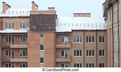 Snow against brick house. Winter.