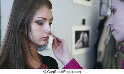 Make-up - Making up the model for photo session in studio.