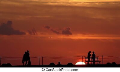 people on a pier in silhouette as the sun sets behind them, cozumel, mexico