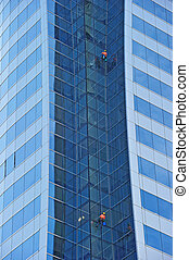 Workers suspended on a scaffold high up on a blue glass...