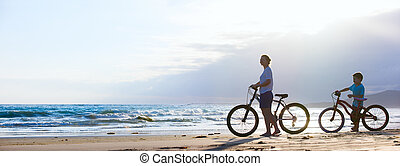 Mother and son biking at beach - Panorama of mother and son...