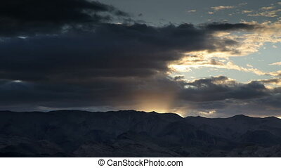 view of a mountain range in death valley at sunset,...