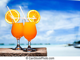 Two bocals of Tequila Sunrise cocktails on a beach table...