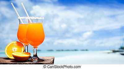 Two bocals of Tequila Sunrise cocktail on a beach table near...