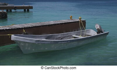 a small fishing boat moored in beautiful caribbean water