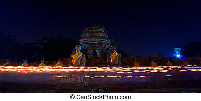 Walking with lighted candles in hand around a temple candle...