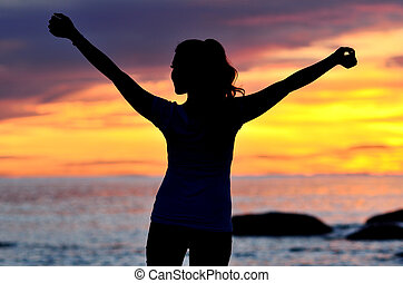 Young woman raising her hands while standing silhouetted against the sunrise.