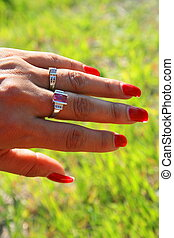 Womans Hand - Womans hand with gold rings over green grass...
