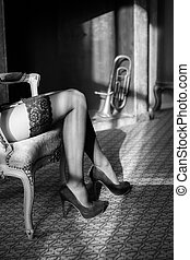 Luscious legs - Young ladybsitting in a chair wearing black...