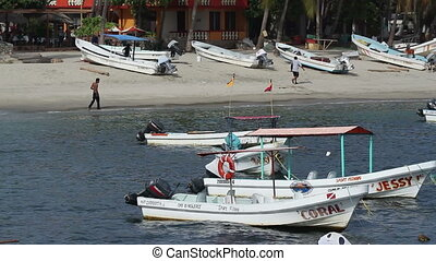 small fishing boats in the harbour in puerto escondido,...