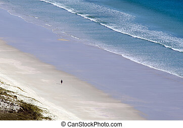 Person on empty beach on an Island - Aerial view of one...