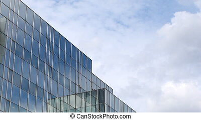 reflections of clouds moving in glass mirrored office tower