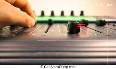 hands moving faders on music equipment