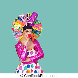 Pensive girl clown with a big colorful wig