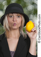 Woman Holding Lemon - Beautiful woman puckering her lips...