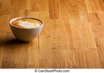 Cappuccino - A warm specialty coffe on a wood table