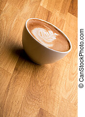 Cafe Latte - A cappuccino with latte art on a wooden table