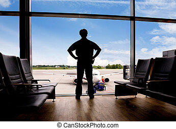 Waiting at Airport - A male waits in a terminal at an...