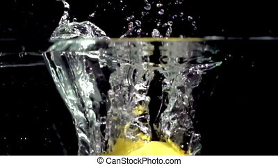 fresh lemon fruit dropped into water shot in super slow...