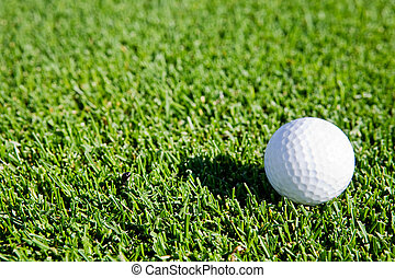 Golf Ball Background - A golf ball sitting on green grass -...