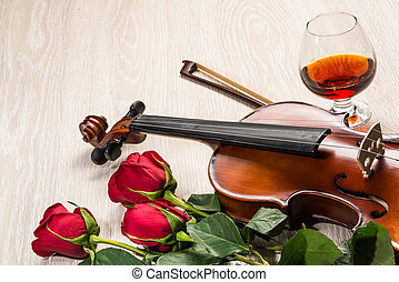 Violin, rose, glass and music books, still life