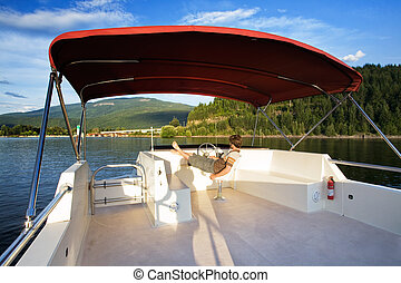 House boat on Lake - A young male driving a house boat from...