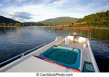Luxury on a Lake - A young male at the helm of a luxury boat