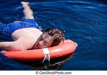 Exhausted Swimmer - A swimmer laying exhausted on a life...