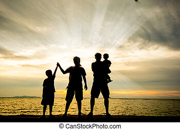 silhouette of happy family at the beach