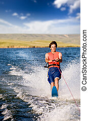 Water Skiing - A man water skiing on a lake
