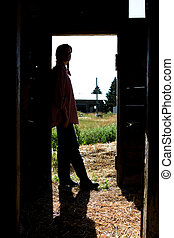 Farm Girl Silhouette - A farm girl standing in a doorway of...