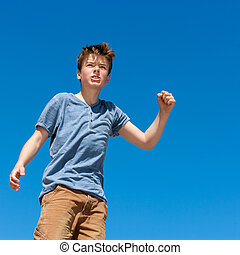 Upset boy raising fist outdoors. - Close up portrait of...