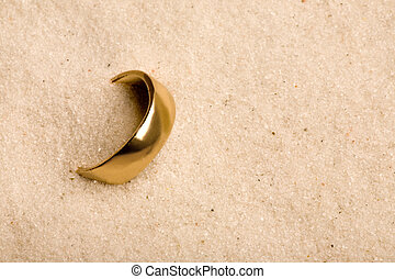 Wedding Ring in Sand - A wedding ring buried in the sand -...