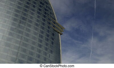 glass hotel in barcelona with clouds rushing by
