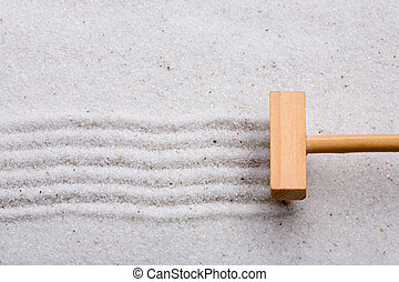 Rake Sand - A small rake, creating a design in a zen garden