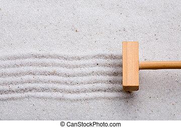 Rake Sand - A small rake, creating a design in a zen garden