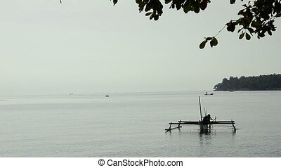 fisherman with boat in morning at bali, indonesia