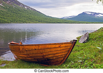 Wooden rowboat at Lapland lake - Boat on a summer evening in...