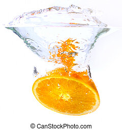 orange falls into the water covered with splashes and...