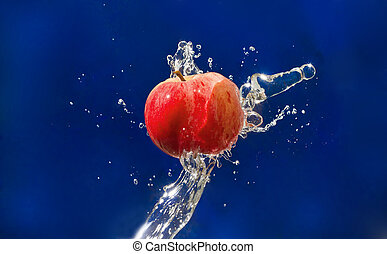 Red Apple drops in the jet of water sprays on blue texture