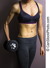Athletic young woman with dumbbell