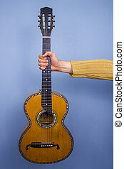 Old guitar held by an outstretched arm